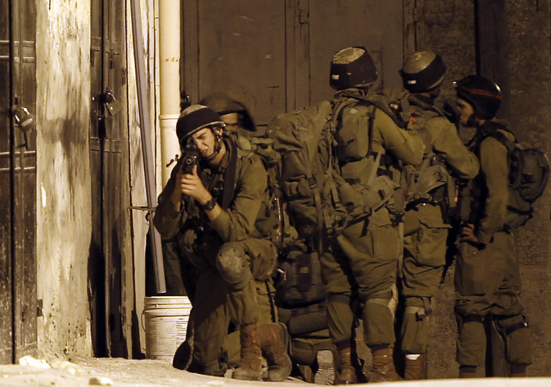 Israeli soldiers take part in a search operation in the West Bank village of Awarta on June 26, 2014