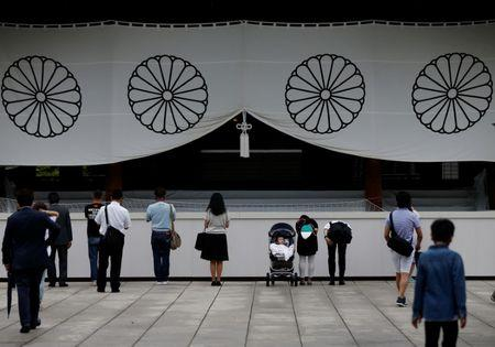 Visitors bow while paying tribute to the war dead at Yasukuni Shrine in Tokyo