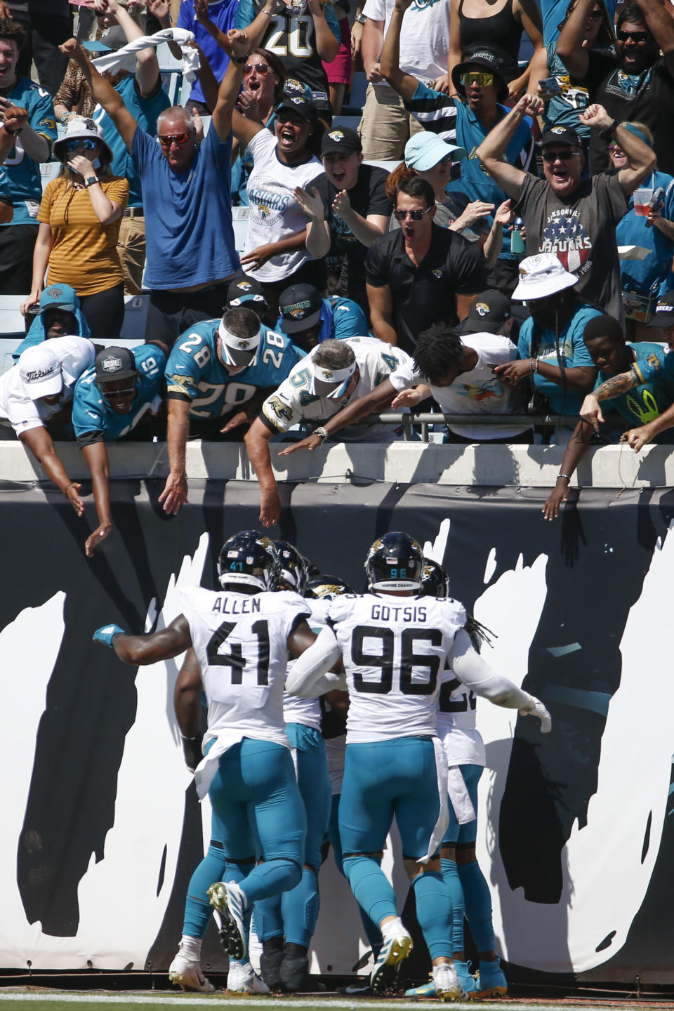 Fans celebrate with Jacksonville Jaguars players after wide receiver Jamal Agnew ran a missed field goal attempt against the Arizona Cardinals back for a 109-yards for a touchdown during the first half of an NFL football game, Sunday, Sept. 26, 2021, in Jacksonville, Fla. (AP Photo/Stephen B. Morton)
