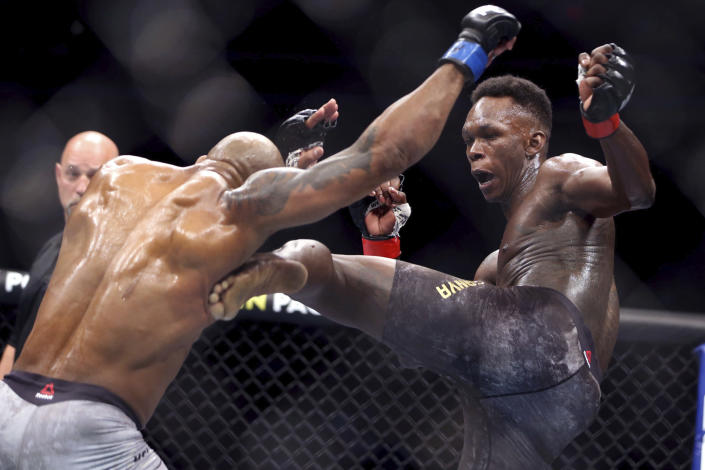 FILE - In this March 7, 2020, file photo, UFC middleweight champion Israel Adesanya of Nigeria, kicks challenger Yoel Romero of Cuba during the second round of their UFC 248 mixed martial arts fight at the T-Mobile Arena in Las Vegas. Adesanya will put his middleweight title on the line in a rematch with Marvin Vettori at UFC 263 on Saturday. (L.E. Baskow/Las Vegas Review-Journal via AP, File)