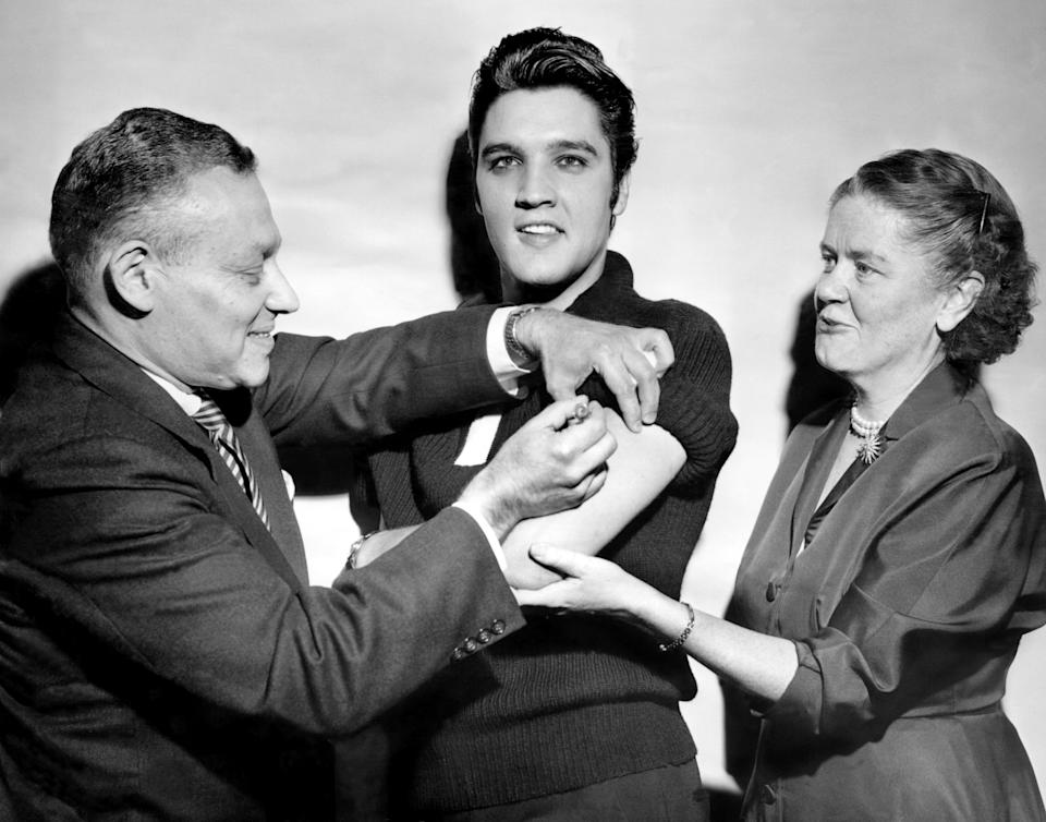 Elvis Presley receives a polio vaccination from Dr. Leona Baumgartner and Dr. Harold Fuerst at CBS studio 50 in New York City.