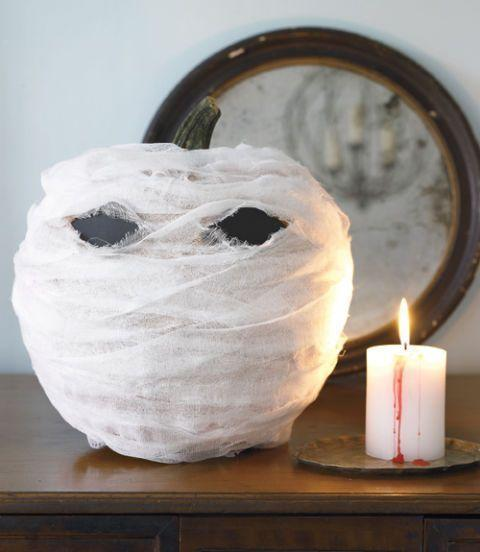 """<p>Want to decorate your home with pumpkins but don't want pull out the knives to carve them? Grab cheese cloth and wrap it around your pumpkins, and you should be good to go.</p><p><em><a href=""""https://www.womansday.com/home/crafts-projects/how-to/a5999/craft-project-menacing-mummy-123881/"""" rel=""""nofollow noopener"""" target=""""_blank"""" data-ylk=""""slk:Get the tutorial for Menacing Mummy."""" class=""""link rapid-noclick-resp"""">Get the tutorial for Menacing Mummy.</a></em></p>"""