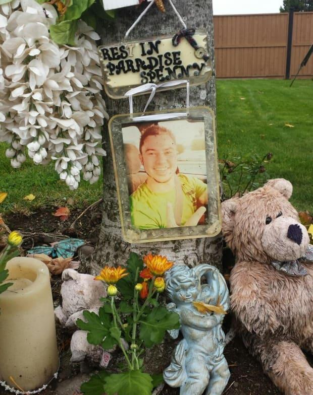 Spencer Alexander Moore was the victim of a 2019 hit and run. A photo is seen on display at a roadside memorial.