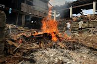 Typhoon survivors burn the debris of destroyed houses in Tacloban, Leyte province on December 7, 2013