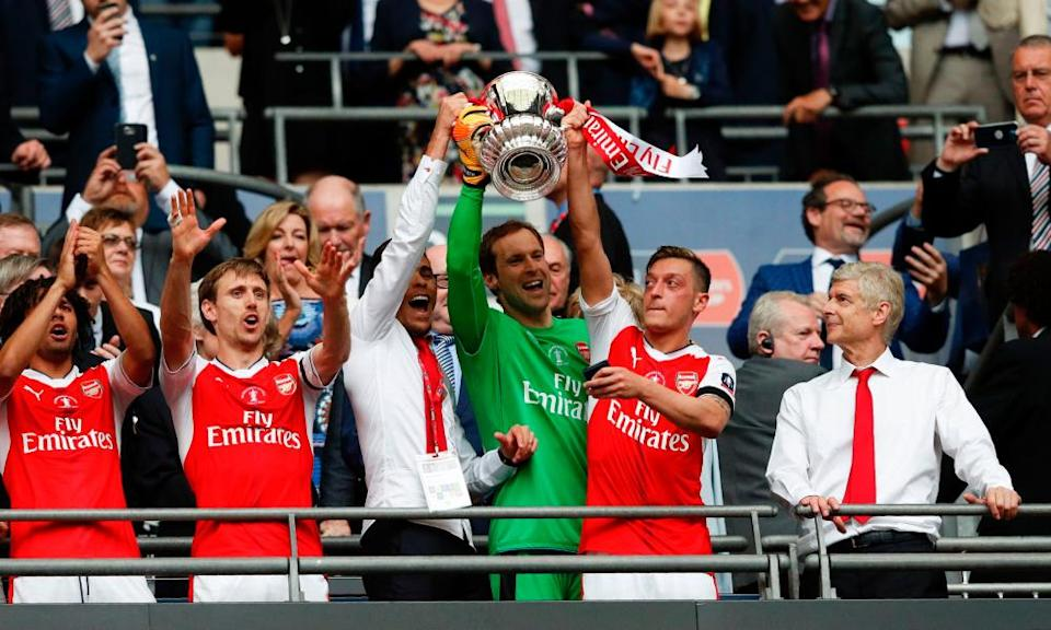 Arsenal's Gabriel Paulista, Petr Cech and Mesut Özil lift the FA Cup as Arsène Wenger looks on after the 2-1 win over Chelsea in 2017.