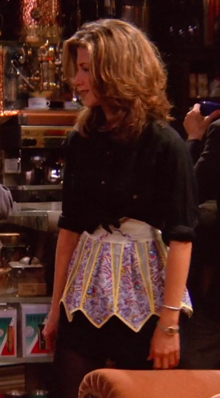 Rachel wearing tights, a miniskirt, an apron, and a long-sleeve button-up tied to be a crop top