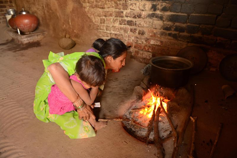 An Indian villager, holding her child, blows air to ignite her traditional village stove at her home in Keiyal on November 29, 2012 (AFP Photo/Sam Panthaky)
