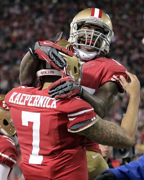 San Francisco 49ers quarterback Colin Kaepernick (7) celebrates after running for touchdown with tight end Vernon Davis during the first quarter of an NFC divisional playoff NFL football game against the Green Bay Packers in San Francisco, Saturday, Jan. 12, 2013. (AP Photo/Tony Avelar)