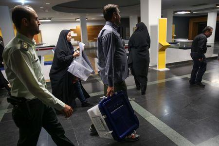 An electoral worker carries a ballot box after closing vote in a polling station in Tehran