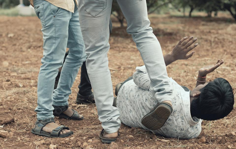 Concept of mob lynching - Group of people bullying, kicking a man - Close up of young adult males hitting a person on ground.
