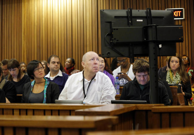 Media look at photographs of the crime scene at the home of Oscar Pistorius in court during his murder trial in Pretoria, South Africa, Friday, March 14, 2014. Pistorius is charged with the shooting death of his girlfriend Reeva Steenkamp, on Valentines Day in 2013. (AP Photo/Kim Ludbrook, Pool)