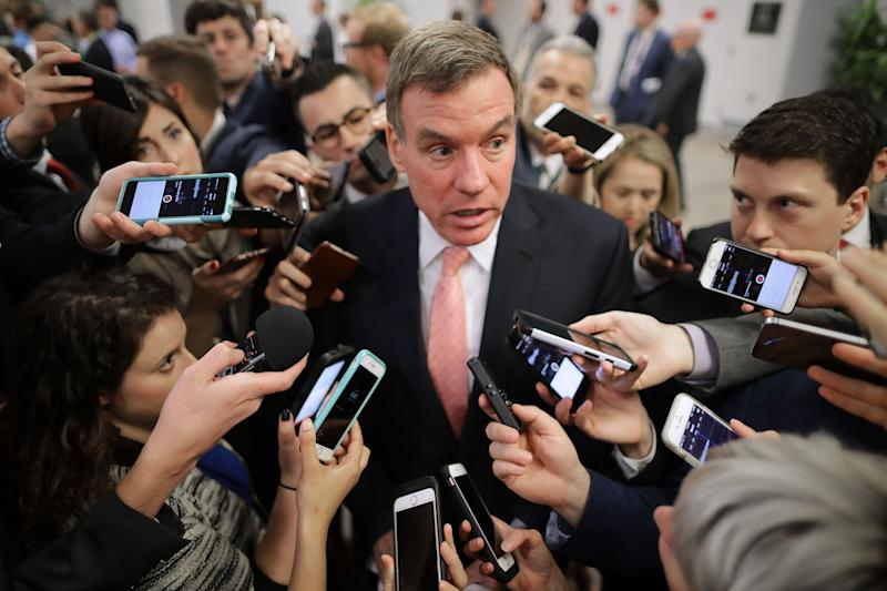 Reporters surround Senate intelligence committee ranking member Sen. Mark Warner as he heads for a policy luncheon in Washington on May 16.