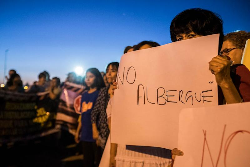 Residents of Mexicali, Mexico, gather Monday, Oct. 14, 2019, to protest the possible opening of a migrant shelter for migrants from Central America who are waiting for a court hearing in the U.S. in order to seek asylum. The residents are worried about the migrants devaluing their property, possible violence and the safety of school age children.