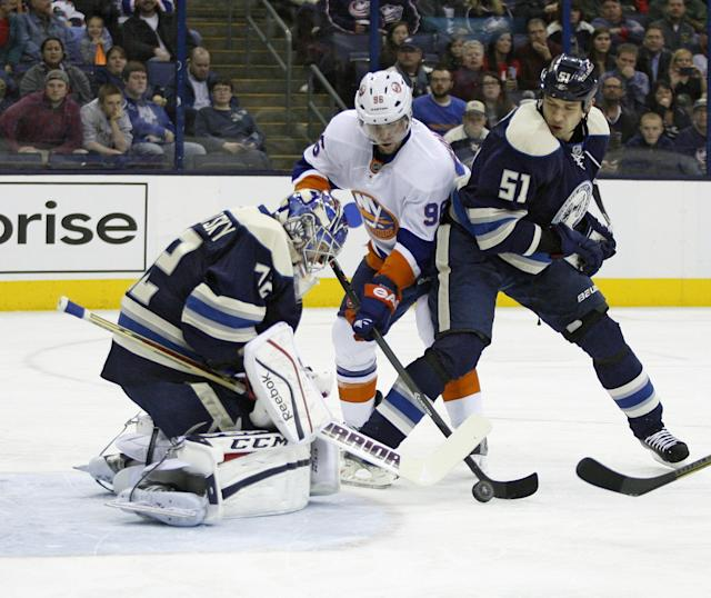 Columbus goalie Sergei Bobrovsky (72), of Russia, blocks a shot by New York Islanders' Pierre-Marc Bouchard (96) as teammate Fedor Tyutin (51) helps during the first period of an NHL hockey game Saturday, Nov. 9, 2013, in Columbus, Ohio. (AP Photo/Mike Munden)