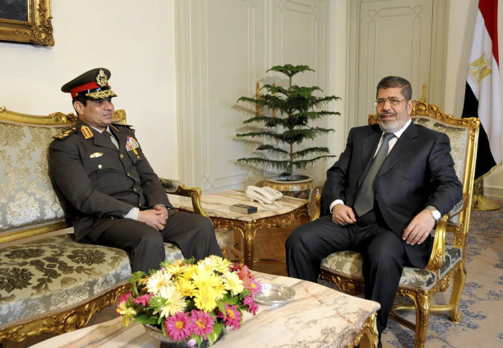 FILE - In this Thursday Feb, 21, 2013 file photo, released by the Egyptian Presidency, Egyptian Minister of Defense, Lt. Gen. Abdel-Fattah el-Sissi, left, meets with Egyptian President Mohammed Morsi at the presidential headquarters in Cairo, Egypt. A year ago, Egypt's opposition and youth movements demanded the then-ruling military leave power. Now some are counting on its protection as they try to remove Islamist President Mohammed Morsi with a wave of protests. They're hoping the generals, who have signaled discontent with the president, will pressure him out without outright taking over. But Morsi's Islamist backers are already angrily denouncing what they call a potential coup against an elected leader. (AP Photo/Mohammed Abd El Moaty, Egyptian Presidency, File)