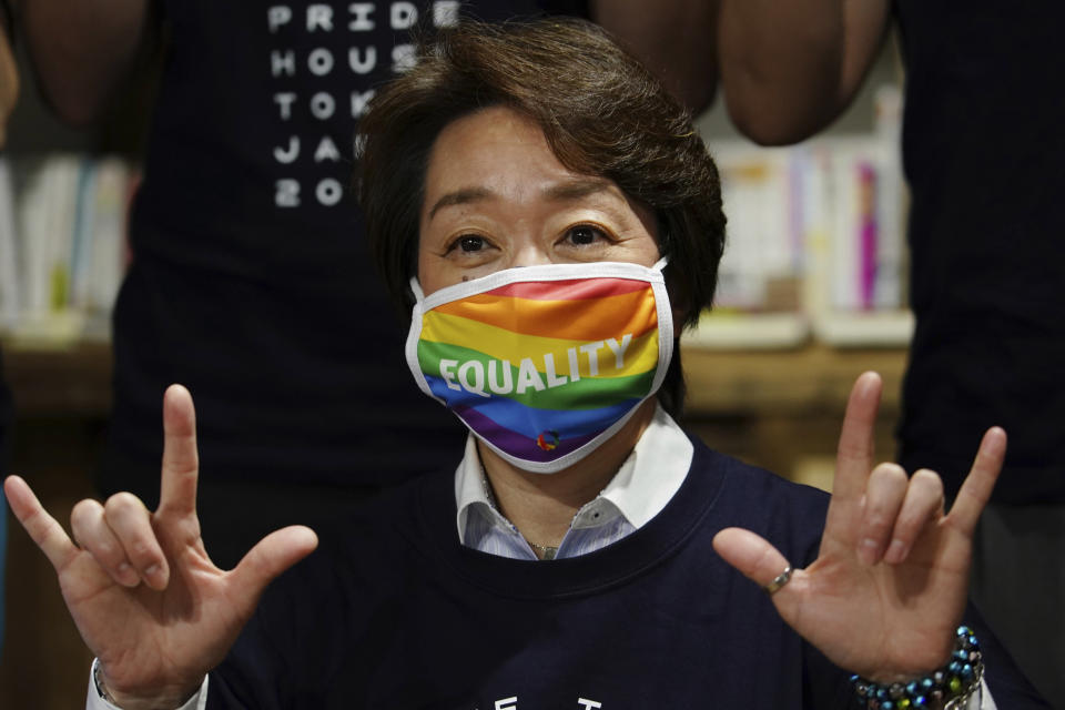 """Tokyo 2020 Organizing Committee President Seiko Hashimoto wearing a rainbow-colored mask with word """"Equality"""" poses for a photo with representatives and staff at Pride House Tokyo Legacy during her visit, in Tokyo Tuesday, April 27, 2021. Japan marked LGBTQ week with pledge to push for equality law before the Olympics. (AP Photo/Eugene Hoshiko, Pool)"""