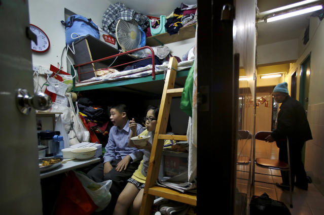 In this Jan. 25, 2013 photo, 63-year-old Lee Tat-fong, walks in a corridor while her two grandchildren Amy, 9, and Steven, 13 sit in their 50-square-foot room in Hong Kong. Lee, like many poor residents, has applied for public housing but faces years of waiting. Nearly three-quarters of 500 low-income families questioned by Oxfam Hong Kong in a recent survey had been on the list for more than 4 years without being offered a flat. (AP Photo/Vincent Yu)