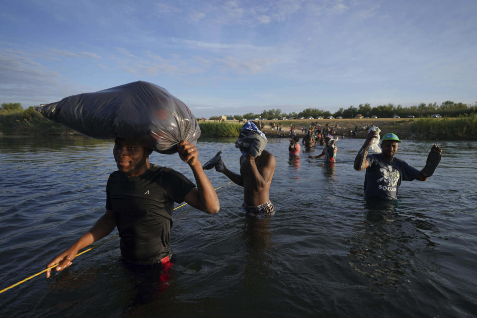Migrants, many from Haiti, wade across the Rio Grande river to leave Del Rio, Texas, and return to Ciudad Acuna, Mexico, early Wednesday, Sept. 22, 2021, some to avoid possible deportation from the U.S. and others to load up with supplies. (AP Photo/Fernando Llano)