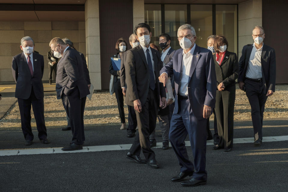 "IOC President Thomas Bach, foreground, wearing a protective mask gestures to journalists during a visit to Olympic and Paralympic Village in Tokyo Tuesday, Nov. 17, 2020. Bach said during this week's trip to Tokyo that he is ""encouraging"" all Olympic ""participants"" and fans to be vaccinated - if one becomes available - if they are going to attend next year's Tokyo Olympics. (Nicolas Datiche/Pool Photo via AP)"