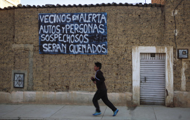 """In this Aug. 17, 2013 photo, a boy runs past a sign that reads in Spanish """"Neighbors on alert. Suspicious cars and people will be burned"""" in El Alto, Bolivia. Mob violence erupts sporadically across Latin America in places where close-knit communities feel unprotected by police. (AP Photo/Juan Karita)"""