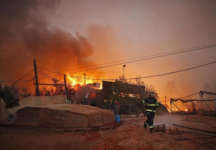 Firefighters helps extinguish a new fire that broke out in the Israeli town of Nataf, west of the Arab Israeli town of Abu Ghosh, along the border with the occupied West Bank on November 25, 2016 (AFP Photo/Ahmad Gharabli)