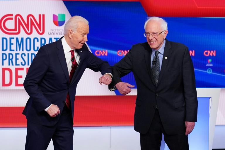Democratic presidential hopefuls Joe Biden (L) and Bernie Sanders greet each other with an elbow bump at the start of their debate