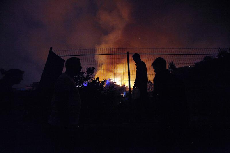 People watch as a forest fire rages towards urban areas in the city of Valparaiso, Chile, Sunday, April 13, 2014. Authorities say the first fire has destroyed at least 150 homes and is forcing evacuations. ( AP Photo/ Luis Hidalgo)