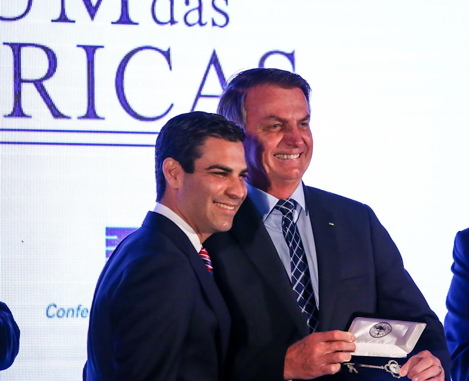 Miami Mayor Francis Suarez gives Brazilian President Jair Bolsonaro(R) the keys to the city during the Forum Of The Americas at the InterContinental Miami in Miami, Florida on March 10, 2020. (Photo by Zak BENNETT / AFP) (Photo by ZAK BENNETT/AFP via Getty Images)