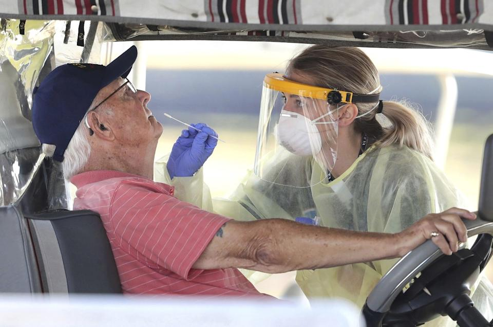 A medical student uses a nasal swab to test a resident of the Villages, Fla., for coronavirus infection.