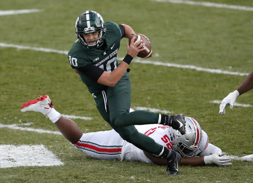 Michigan State quarterback Payton Thorne (10) scrambles against Ohio State's Kyle King (52) during the second half of an NCAA college football game, Saturday, Dec. 5, 2020, in East Lansing, Mich. Ohio State won 52-12. (AP Photo/Al Goldis)