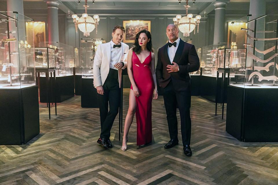 Dwayne Johnson, Gal Gadot, and Ryan Reynolds wearing evening garb as they stand in a room full of weapons in glass cases