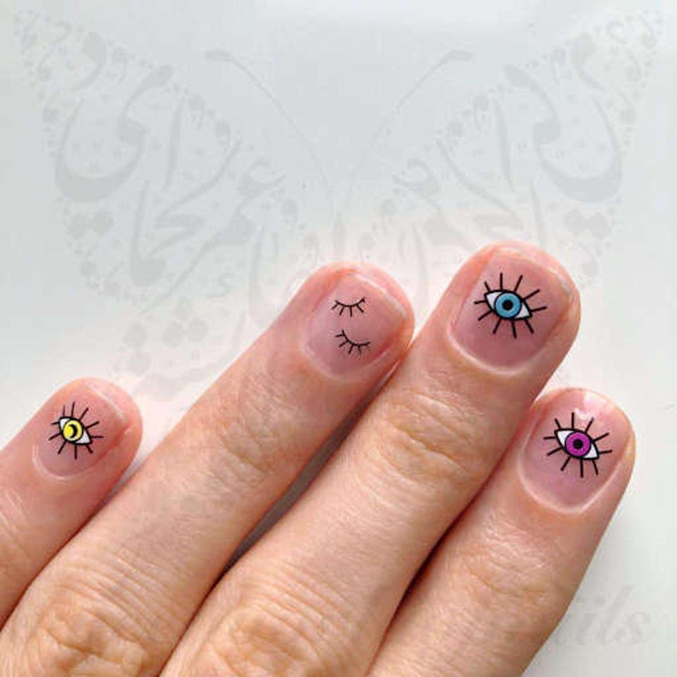 """<p><strong>SWNails</strong></p><p>etsy.com</p><p><strong>$3.33</strong></p><p><a href=""""https://go.redirectingat.com?id=74968X1596630&url=https%3A%2F%2Fwww.etsy.com%2Flisting%2F794559181%2Fevil-eye-nail-art-blue-red-green-eye&sref=https%3A%2F%2Fwww.oprahdaily.com%2Fbeauty%2Fskin-makeup%2Fg33239588%2Fhalloween-nail-ideas%2F"""" rel=""""nofollow noopener"""" target=""""_blank"""" data-ylk=""""slk:SHOP NOW"""" class=""""link rapid-noclick-resp"""">SHOP NOW</a></p><p>Recreate the trendy evil eye manicure all by yourself for Halloween this year. These easy decals work on bare nails, or on top of a polish of your choice. Just make sure to top with a clear coat so that they last a long time.</p>"""