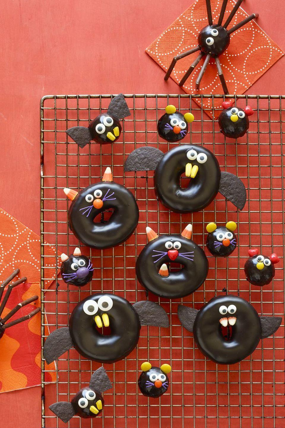 """<p>Pressed on time? Look no further than these store-bought doughnuts outfitted with candy corn, M&Ms, and more.</p><p><strong><em><a href=""""https://www.womansday.com/food-recipes/food-drinks/a23460042/black-cat-bat-spider-and-mice-doughnuts-recipe/"""" rel=""""nofollow noopener"""" target=""""_blank"""" data-ylk=""""slk:Get the Black Cat, Bat, Spider, and Mice Doughnuts recipe."""" class=""""link rapid-noclick-resp"""">Get the Black Cat, Bat, Spider, and Mice Doughnuts recipe. </a></em></strong></p>"""