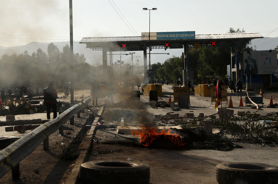 Tires burn at a toll station in Sacaba, Bolivia, Saturday, Nov. 16, 2019. Bolivia's political crisis turned deadly after security forces opened fire on supporters of former President Evo Morales in Sacaba Friday, killing at least five people, injuring dozens and threatening the interim government's efforts to restore stability following the resignation of the former president in an election dispute. (AP Photo/Juan Karita)