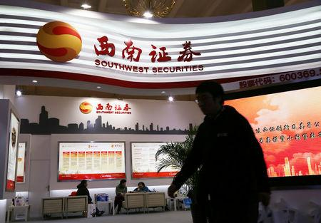Man walks past a booth of Southwest Securities at a finance expo in Beijing