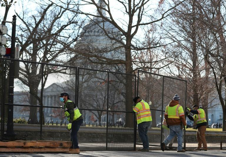 Workers erect a fence around the US Capitol a day after a pro-Trump mob broke into the building