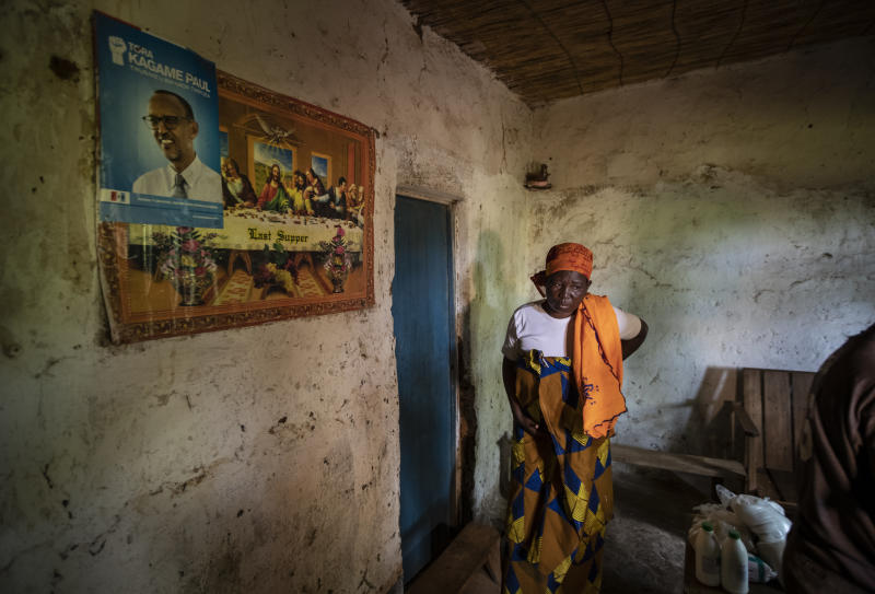 In this photo taken Tuesday, Nov. 5, 2019, Faina Nyirabaguiza, 52, who has cervical cancer, walks slowly and in pain back to her bedroom after being given an increased dose of oral liquid morphine, past posters of Christianity's The Last Supper and of Rwanda's President Paul Kagame, after a visit to check on her health by palliative care nurse Madeleine Mukantagara, at her home in the village of Ruesero, near Kibogora, in western Rwanda. While people in rich countries are dying from overuse of prescription painkillers, people in Rwanda and other poor countries are suffering from a lack of them, but Rwanda has come up with a solution to its pain crisis - it's morphine, which costs just pennies to produce and is delivered to households across the country by public health workers. (AP Photo/Ben Curtis)