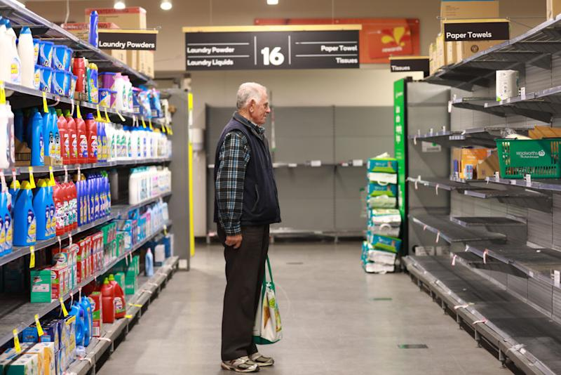 An elderly man looks at almost empty shelves at Woolworths.