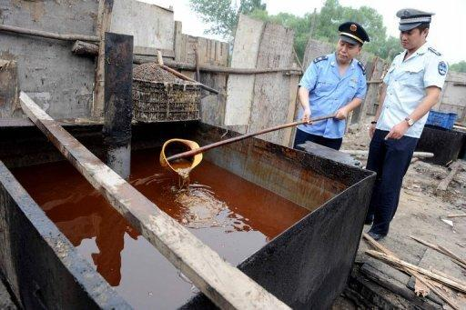 Chinese police inspect illegal cooking oil that was seized in 2010 during a crackdown in Beijing after reports said up to one-tenth of Chinese supplies were illegally made and contained cancer-causing agents. Decades of industrial development greased by corruption has produced unprecedented levels of pollution and an epidemic of toxic foodstuffs, made and marketed by ruthless entrepreneurs