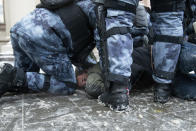 Police officers detain a man during a protest against the jailing of opposition leader Alexei Navalny in Moscow, Russia, on Sunday, Jan. 31, 2021. Tens of thousands of people are protesting across Russia to demand the release of jailed opposition leader Alexei Navalny in wave of nationwide demonstrations that have rattled the Kremlin. Many chanted slogans against President Vladimir Putin. Activists say police detained more than 3,300 protesters across the country on Sunday, including over 900 in Moscow. (AP Photo/Denis Kaminev)