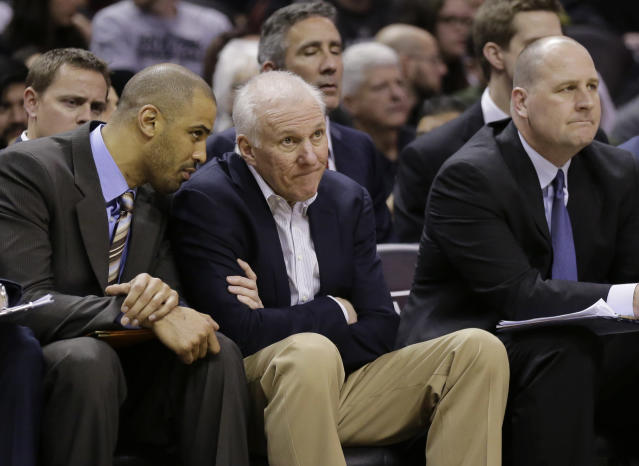 San Antonio Spurs coach Gregg Popovich, center, sits with assistant coaches Ime Udoka, left, and Jim Boylen, right, during the second half of an NBA basketball game against the Milwaukee Bucks, Sunday, Jan. 19, 2014, in San Antonio. San Antonio won 110-82. (AP Photo/Eric Gay)