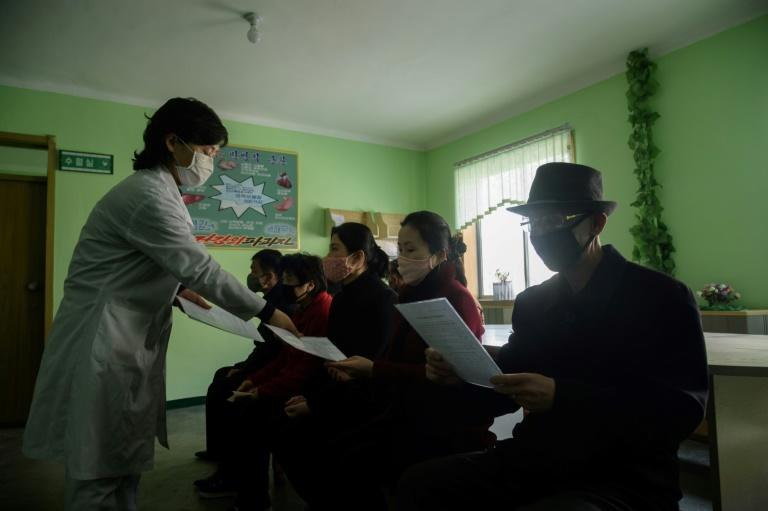 A doctor disseminates information about the coronavirus to people in a waiting room at the Pyongchon District People's Hospital in Pyongyang