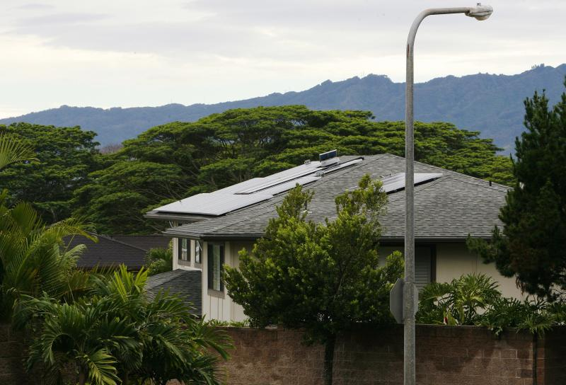 A view of houses with solar panels in the Mililani neighbourhood on the island of Oahu in Mililani, Hawaii, December 15, 2013. A new rule went into effect in September that requires homeowners on Oahu - Hawaii's most populous island - to get the utility's approval before installing photovoltaic rooftop solar systems. In areas like Mililani, the utility's power circuits have reached a threshold where it would be dangerous to add PV systems without investing in upgrades to the distribution system. Picture taken December 15, 2013. To match Analysis SOLAR-HAWAII/ REUTERS/Hugh Gentry (UNITED STATES - Tags: ENERGY BUSINESS)