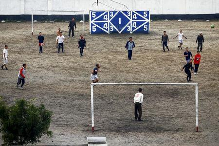FILE PHOTO: People play football in Pyongyang's suburbs, October 11, 2015. REUTERS/Damir Sagolj/File Photo