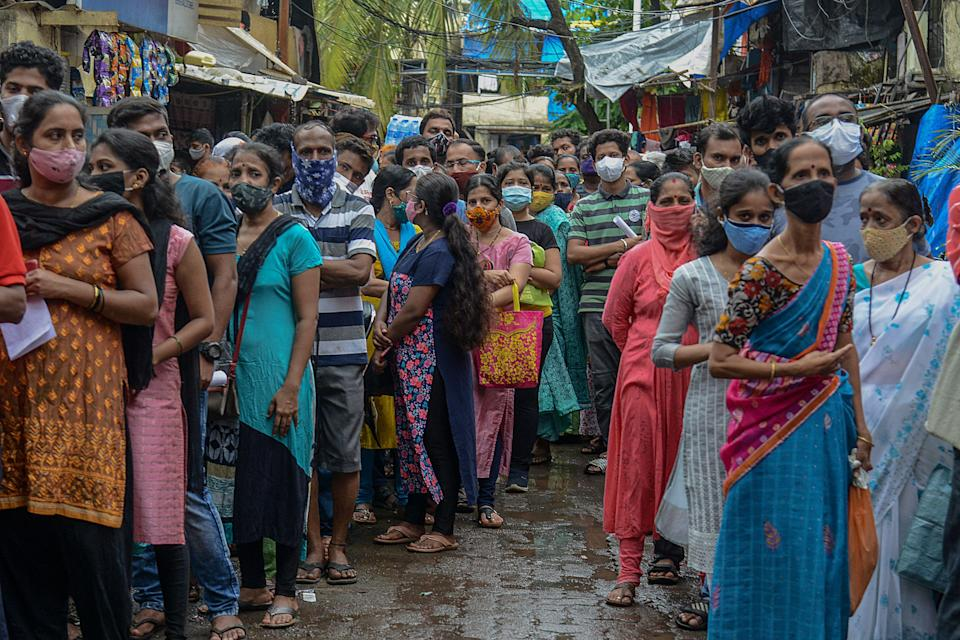 People queue up to get themselves inoculated at a residential settlement in Mumbai on 2 August 2021 (AFP via Getty Images)