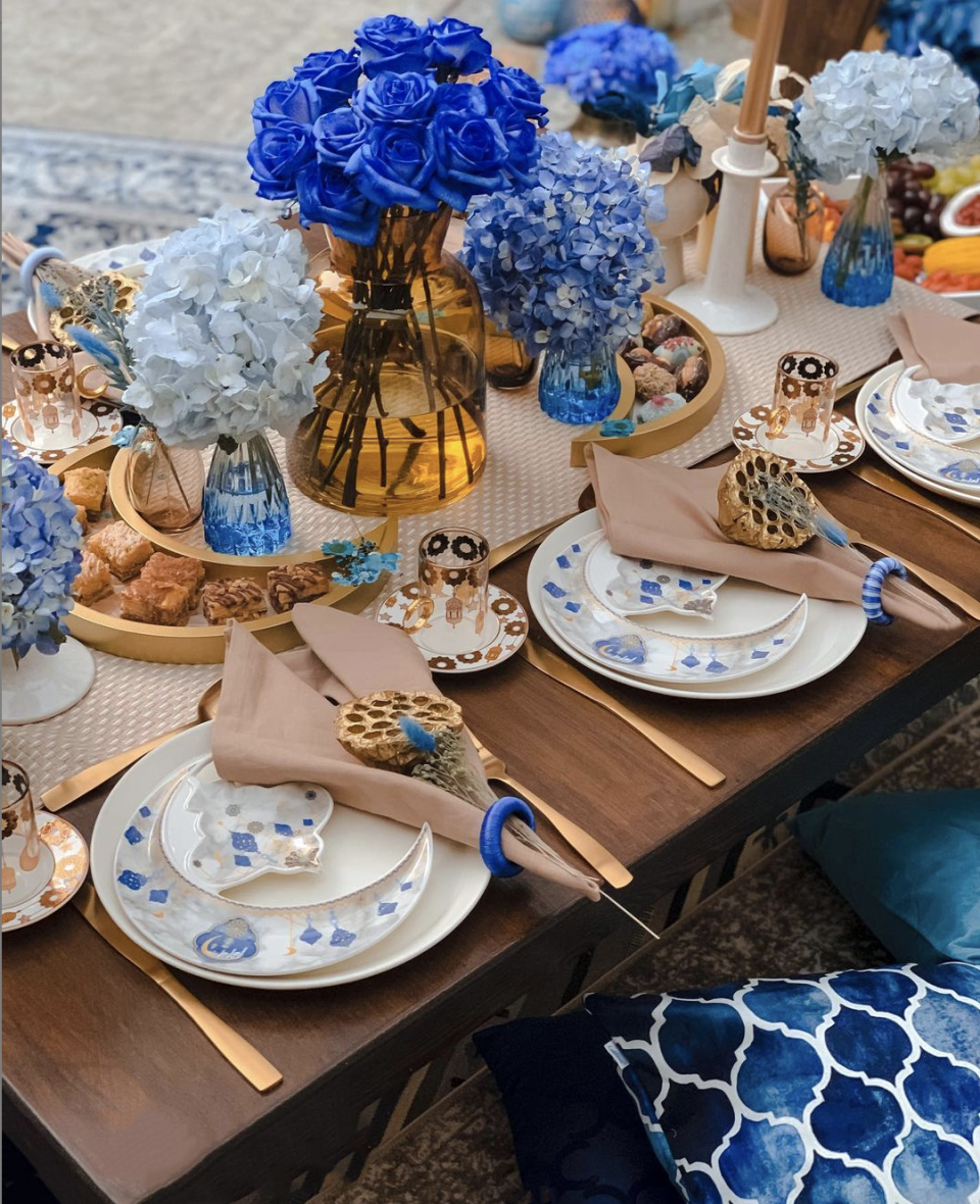 """<p>Pulled from the watercolored ceramic plates, the bold blue varies in saturation to add levels to this table setting by <a href=""""https://www.instagram.com/p/COLtShHFlhb/"""" rel=""""nofollow noopener"""" target=""""_blank"""" data-ylk=""""slk:Ornate Moments"""" class=""""link rapid-noclick-resp"""">Ornate Moments</a>. Kick it up a notch by pulling similar tones for accessories like napkin rings and floor pillows.</p>"""
