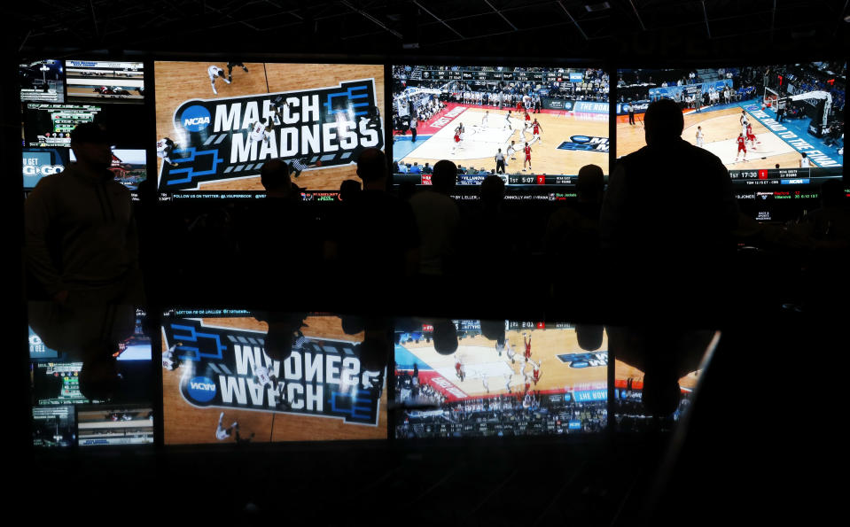 Fans watch the first round of the NCAA college basketball tournament at the Westgate Superbook sports book in Las Vegas on March 15, 2018. (AP/John Locher)