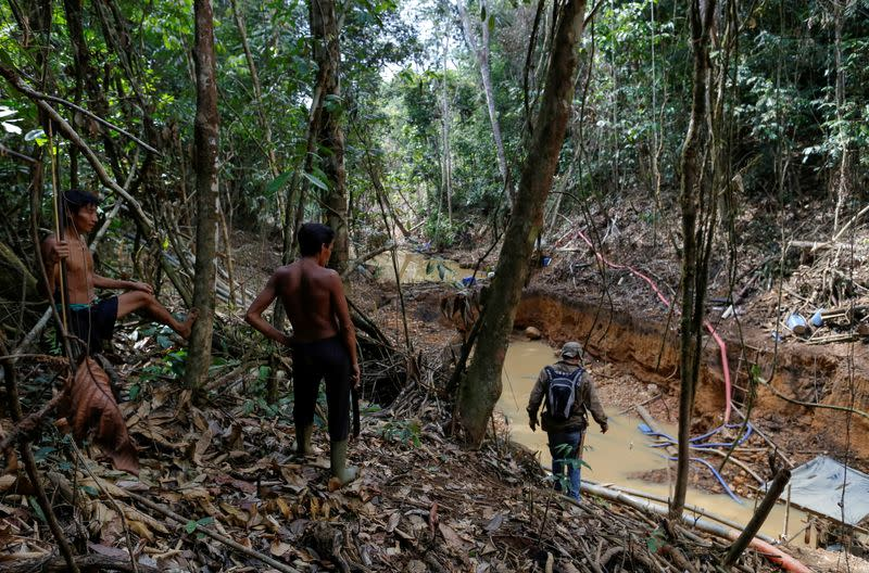 FILE PHOTO: Yanomami indians follow agents of Brazil's environmental agency in a gold mine during an operation against illegal gold mining on indigenous land, in the heart of the Amazon rainforest