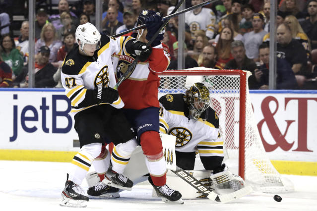 Boston Bruins goaltender Jaroslav Halak, right, stops the puck as defenseman Torey Krug (47) defends during the second period of an NHL hockey game against the Florida Panthers, Saturday, Dec. 14, 2019, in Sunrise, Fla. (AP Photo/Lynne Sladky)