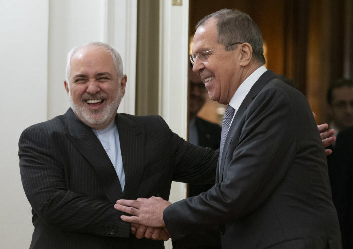 Russian Foreign Minister Sergey Lavrov, right, and Iranian Foreign Minister Mohammad Javad Zarif smile as they enter a hall for theil talks in Moscow, Russia, Monday, Dec. 30, 2019. (AP Photo/Alexander Zemlianichenko)